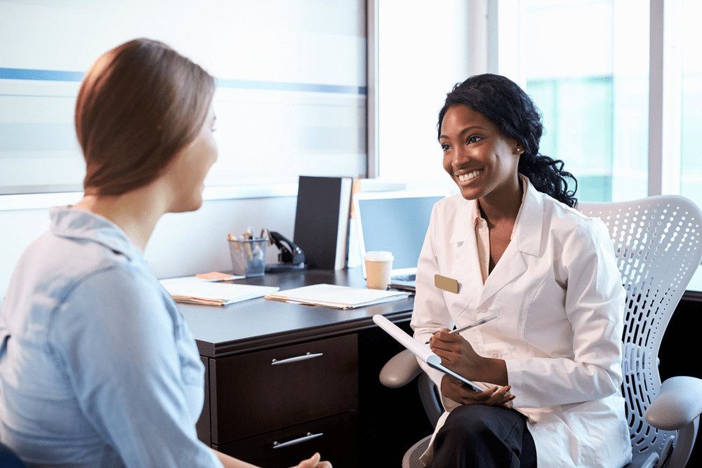 Female doctor speaking with female patient